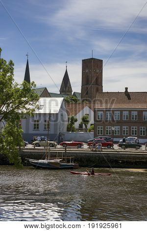 RIBE DENMARK - JUNE 17 2017: Cathedral old houses vintage cars and kayak in river in royal town Ribe Denmark