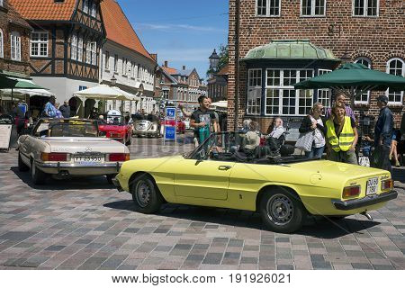 RIBE DENMARK - JUNE 17 2017: Retro cars old houses and people in royal town Ribe Denmark