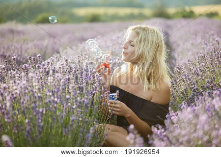 Beautiful woman blowing soap bubbles in lavender field. Magnificent lavender field on the background. Magical sunset colours.