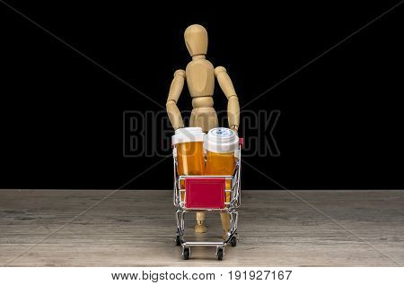 Wooden human mannequin holding shopping trolley filled with pill bottles