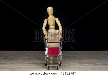 Wooden human mannequin holding shopping trolley filled with parcels