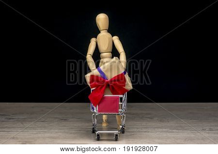 Wooden human mannequin holding shopping trolley with a Christmas present
