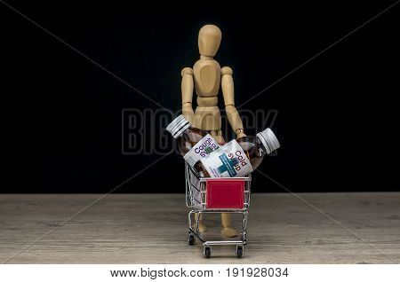 Wooden human mannequin holding shopping trolley filled with cold medicine and flu syrup bottles