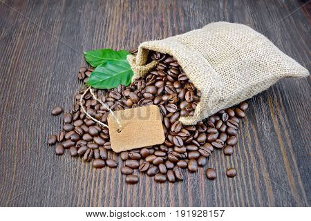 Bag of black coffee beans, tag and green leaves on a wooden board background