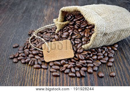 Bag of black coffee beans, tag on the background of a wooden board