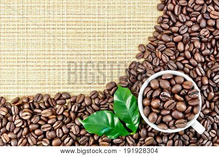 A frame of black coffee beans with green leaves and a cup on a yellow coarse woven fabric