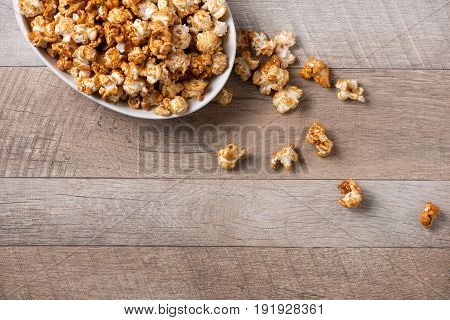 Caramel opcorn in bowl on the wooden table.