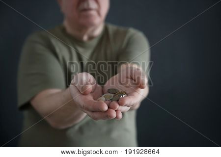 Senior man with coins on dark background, closeup. Poverty concept