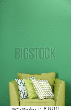 Cozy armchair with pillows on green background