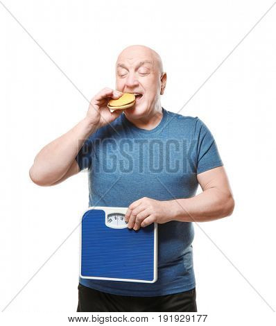 Fat senior man with scales and hamburger on white background. Weight loss concept