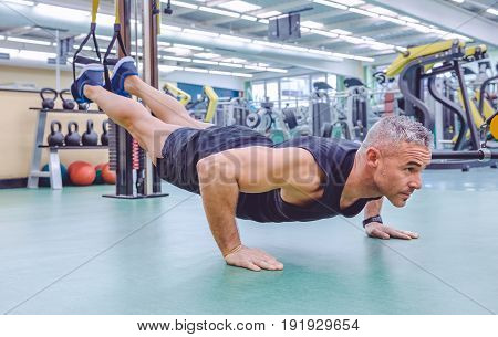 Handsome man doing hard suspension training with fitness straps in a fitness center. Healthy and sporty lifestyle concept.