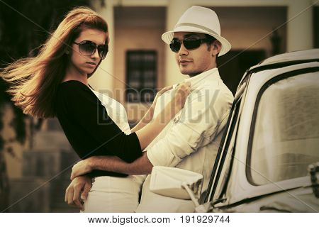 Happy young couple in love next to vintage car. Stylish fashion model in sunglasses outdoor