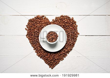 Coffee love concept. Top view of roasted brown coffee beans in heart shape with coffee cup in center on white wooden background