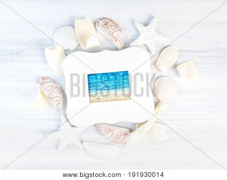 Sea View Picture In White Vintage Picture Frame On Group Of Sea Beach Nautilus Accessories On Wooden