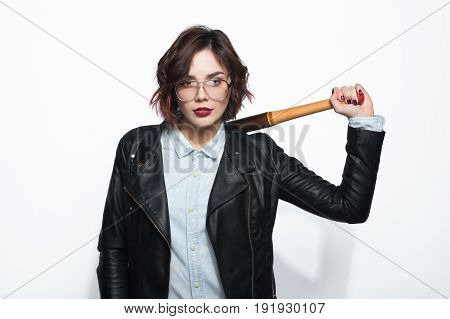 Young stylish brunette in glasses and leather jacket posing with batt on shoulder on white background.