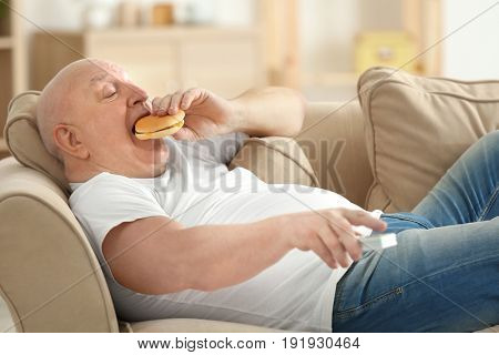 Fat senior man watching TV and eating hamburger while lying on sofa at home. Sedentary lifestyle concept