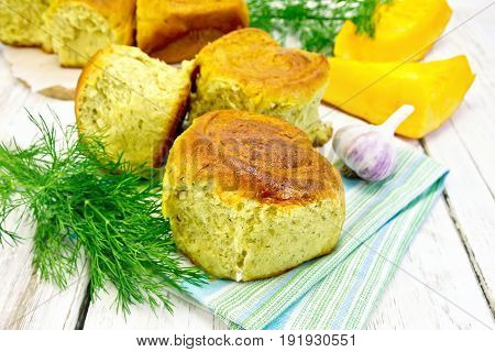 Pumpkin Scones with garlic and dill on a napkin, yellow pumpkin slices on the background of wooden boards