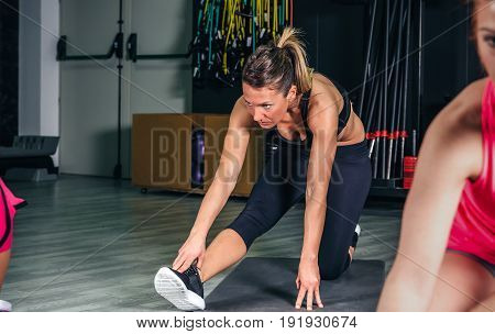 Young woman with pigtail stretching legs in fitness class on sports center