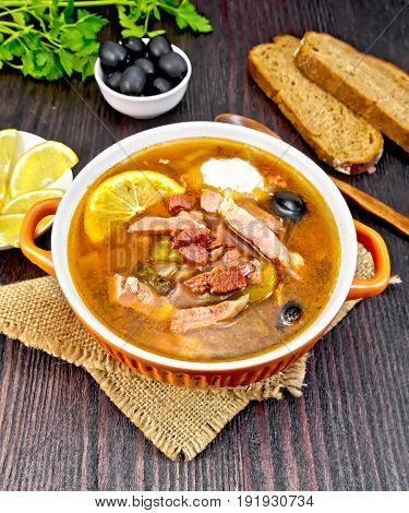 Soup saltwort with lemon, meat, pickles, tomato sauce and olives in a sackcloth, bread and parsley on a dark wooden board