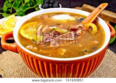 Soup saltwort with lemon, meat, pickles, tomato sauce olives, spoon in a bowl on a sacking on the background of a wooden board