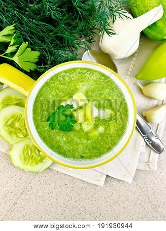 Cucumber soup with green peppers and garlic in a bowl on a yellow napkin, parsley, spoon on a background of a granite table top