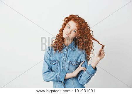 Playful beautiful girl with foxy red hair thinking dreaming biting lips over white background. Copy space.