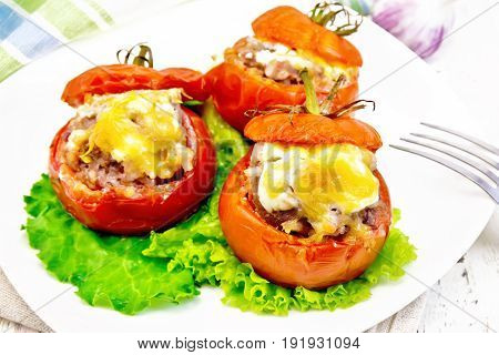 Tomatoes stuffed with meat and rice with cheese on lettuce in a plate, napkin, fork on a light wooden board background