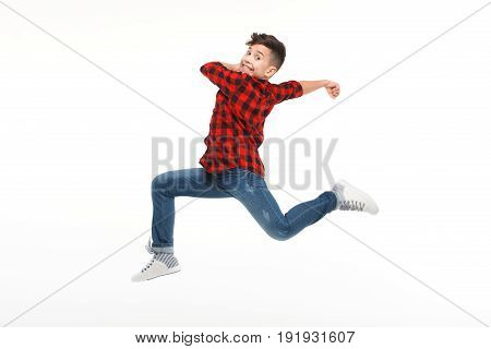 Side view of cheerful boy in casual clothing in moment of jump on white background.