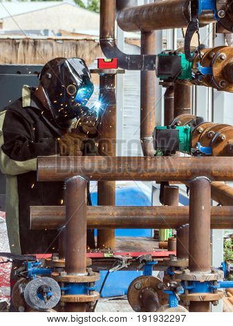 Men welding a rusty pipe in module boiler room