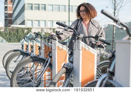 Afro american woman taking a bicycle in a public rental station