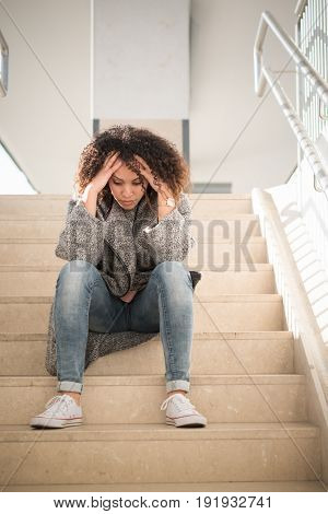 Sad afro american girl seated alone on the stairs