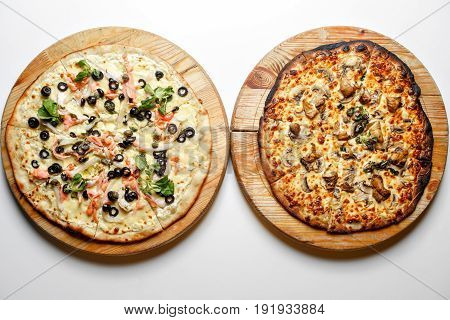 Burnt and normal. Two pizza with tomatoes, salmon, mushroom, pepperoni on wooden rustic background top view.
