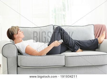 Mature woman watching TV while lying on sofa at home. Sedentary lifestyle concept