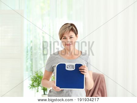 Mature woman with scales at home. Weight loss concept