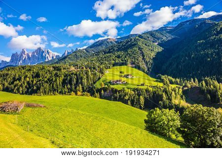 Charming chalet on a green grassy slope. The valley is surrounded by dolomite rocks. Warm autumn in the Dolomites. The concept of ecological tourism