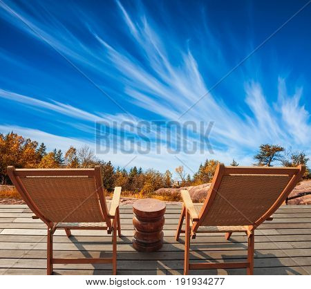 Cirrus clouds in the autumn sky. Lovely place to relax. Two red beach chairs on the riverbank. Old Pinawa Dam Park. The concept of ecological and recreational tourism