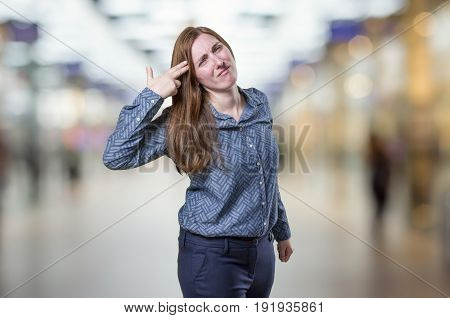 Pretty Business Woman Making Suicide Gesture Over Blur Background