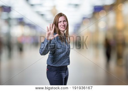 Young Pretty Girl Making Stop Sign Over Blur Background.