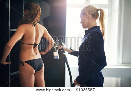 Beauty Professional Providing Spraytan Procedure To Client