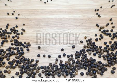 Black peppercorns on wooden table - closeup