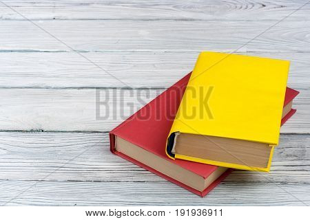 Multi-colored books on a white wooden table