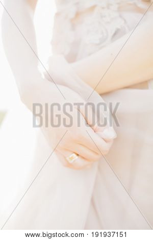 Hands of the bride on a wedding dress on a sunny day. fine art photography.