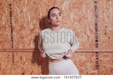 Sexy blonde woman with big breasts in a grey sweatshirt on wooden background. Mock up.