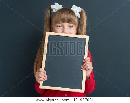 Portrait of adorable little girl with small blackboard at the black chalkboard in classroom.