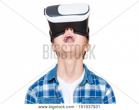 Amazed teen boy wearing virtual reality goggles watching movies or playing video games, on white. Surprised teenager looking in VR glasses. Emotional portrait of child experiencing 3D gadget.