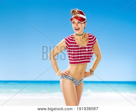 Perfect summer. smiling active woman in red sun visor on the seacoast looking at copy space