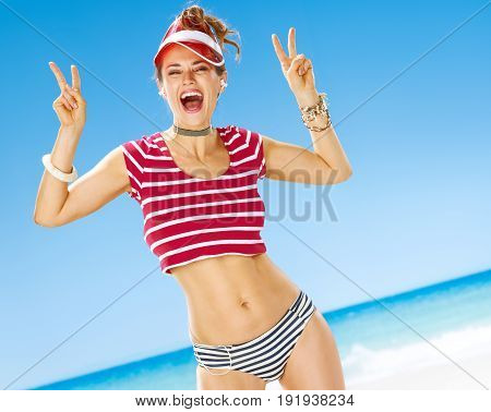 Woman With Headphones Listening To The Music And Showing Victory
