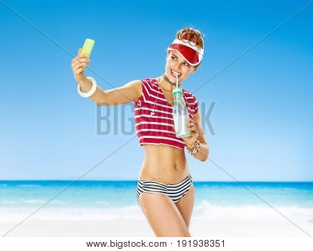 Smiling Healthy Woman In Red Sun Visor On Seashore With Cocktail
