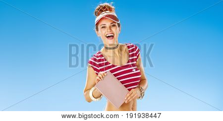 Perfect summer. smiling fit woman in red sun visor on the beach showing book
