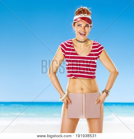 Smiling Woman On Beach Looking At Copy Space Hiding Behind Book